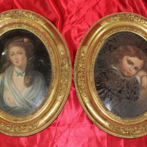 Meravigliosa coppia di ritratti dipinti olio su tela incollata su vetro, con cornici originali in oro zecchino, realizzati in Francia nella seconda metà dell'800.