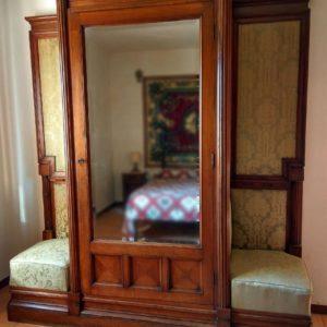 Armadio in legno di noce con sedute laterali realizzato tra gli anni '20 e gli anni '30.